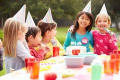 Grupo de crianças que têm a festa de anos exterior Foto de Stock Royalty Free