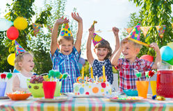 Grupo de crianças que têm o divertimento na festa de anos foto de stock