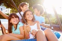 Grupo de crianças que têm o divertimento no balanço no campo de jogos Foto de Stock