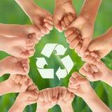 Grupo de crianças que unem as mãos e que reciclam o símbolo contra o fundo borrado ilustração do vetor