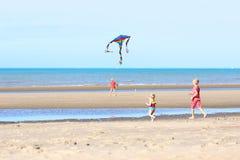 Grupo de crianças que voam o papagaio na praia foto de stock