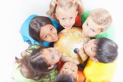 Grupo de crianças internacionais que guardam a terra do globo Fotos de Stock Royalty Free