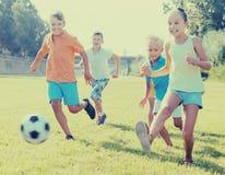 Grupo de crianças positivas que jogam o futebol junto no gramado verde mim Fotografia de Stock
