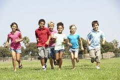 Grupo de crianças que funcionam no parque Fotografia de Stock Royalty Free