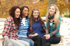 Grupo de cuatro adolescentes que se sientan en banco Imagenes de archivo