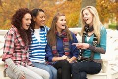 Grupo de cuatro adolescentes que se sientan en banco Fotografía de archivo libre de regalías