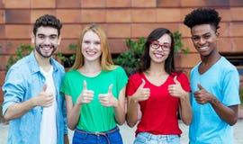 Grupo de cuatro adultos jovenes de la generaci?n y que muestran los pulgares fotos de archivo