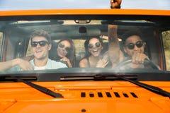 Grupo de cuatro amigos jovenes felices que se sientan en un coche Imágenes de archivo libres de regalías