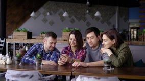 Grupo de cuatro amigos que se sientan en el restaurante junto y que usan el artilugio digital Dos hombres y dos hermosos que sonr almacen de video