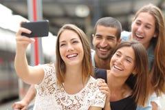 Grupo de cuatro amigos que toman el selfie con un teléfono elegante Fotos de archivo libres de regalías
