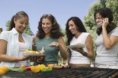 Grupo de cuatro hembras que gozan de una barbacoa fotografía de archivo libre de regalías