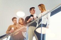 Grupo de cuatro hombres de negocios jovenes en un descanso para tomar café fotografía de archivo libre de regalías