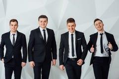 Grupo de cuatro hombres en fondo del blanco de los trajes foto de archivo libre de regalías