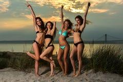 Grupo de cuatro modelos que llevan los bikinis que presentan en la playa de la puesta del sol imagenes de archivo