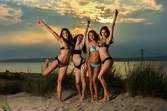 Grupo de cuatro modelos que llevan los bikinis que presentan en la playa de la puesta del sol fotos de archivo libres de regalías