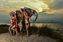 Grupo de cuatro modelos que llevan los bikinis que presentan en la playa de la puesta del sol fotografía de archivo