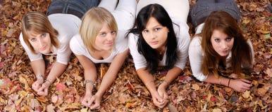Grupo de cuatro muchachas que mienten en hojas de otoño Fotografía de archivo
