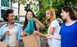 Grupo de cuatro mujeres adultas jovenes que hacen compras en la ciudad Imágenes de archivo libres de regalías