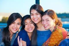 Grupo de cuatro mujeres jovenes que sonríen junto por el lago Foto de archivo libre de regalías