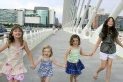Grupo de cuatro niñas que recorre en la ciudad Imagenes de archivo