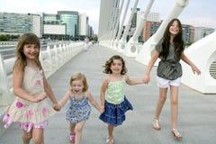 Grupo de cuatro niñas que recorre en la ciudad Fotografía de archivo