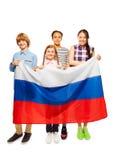 Grupo de cuatro niños adolescentes felices con la bandera rusa Fotografía de archivo