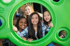 Grupo de cuatro niños con la diversidad cultural que juega junto Foto de archivo libre de regalías
