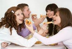 Grupo de cuatro personas con la pizza y el jugo Imágenes de archivo libres de regalías