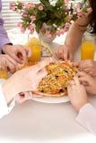 Grupo de cuatro personas con la pizza y el jugo Imagen de archivo