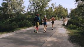 Grupo de cuatro personas que corren en el parque en la salida del sol metrajes
