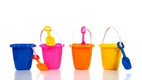 Grupo de cubetas ou de baldes coloridos da praia no branco Imagens de Stock Royalty Free