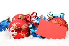 Grupo de decoração vermelha, azul do Natal com o cartão dos desejos na neve Imagens de Stock