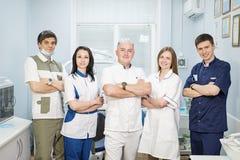 Grupo de dentistas que estão em seu escritório e que olham a câmera imagens de stock royalty free