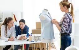 Grupo de desenhadores de moda que trabalham e que decidem detalhes de coleção nova da roupa na oficina costurando fotografia de stock royalty free