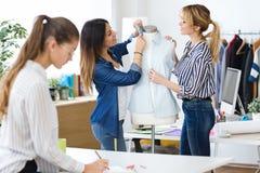 Grupo de desenhadores de moda que trabalham e que decidem detalhes de coleção nova da roupa na oficina costurando foto de stock royalty free