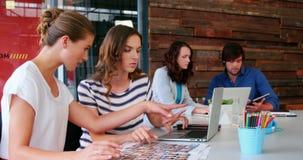 Grupo de designer gráfico que interage ao usar o portátil filme