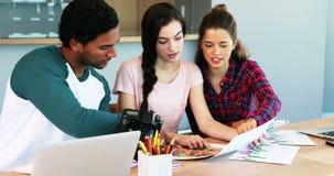 Grupo de designer gráficos que trabalham junto na mesa vídeos de arquivo