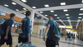 Grupo de desportistas novos que andam através do corredor da construção do aeroporto video estoque