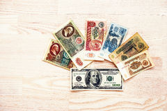 Grupo de dinheiro dos rublos de URSS da conta com 100 dólares no backgro de madeira Fotografia de Stock