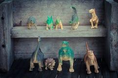 Grupo de dinosaurios en estante de madera Fotos de archivo