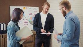 Grupo de diretores empresariais novos que trabalham e que comunicam-se junto no escritório criativo video estoque