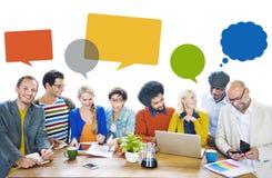 Grupo de diseñadores alegres multiétnicos con las burbujas del discurso Imagenes de archivo