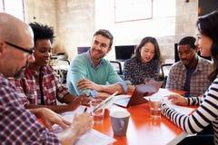 Grupo de diseñadores que tienen reunión alrededor de la tabla en oficina imagen de archivo libre de regalías