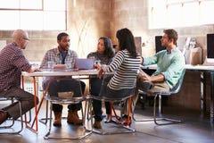 Grupo de diseñadores que tienen reunión alrededor de la tabla en oficina fotografía de archivo libre de regalías