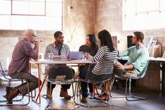 Grupo de diseñadores que tienen reunión alrededor de la tabla en oficina imágenes de archivo libres de regalías