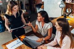 Grupo de diseñadores de sexo femenino creativos que trabajan en un nuevo proyecto junto que habla, discutiendo, sugiriendo las id Fotos de archivo libres de regalías