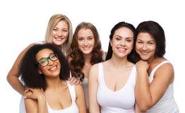 Grupo de diversas mujeres felices en la ropa interior blanca imagenes de archivo