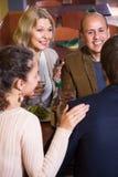 Grupo de diversos amigos de la edad que comen la cena y el vino en el restaur Imagen de archivo libre de regalías