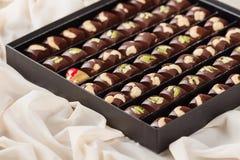 Grupo de doces de chocolate feitos a mão luxuosos na caixa de presente Fotografia de Stock Royalty Free