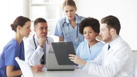 Grupo de doctores con el tablero que hablan en la clínica metrajes